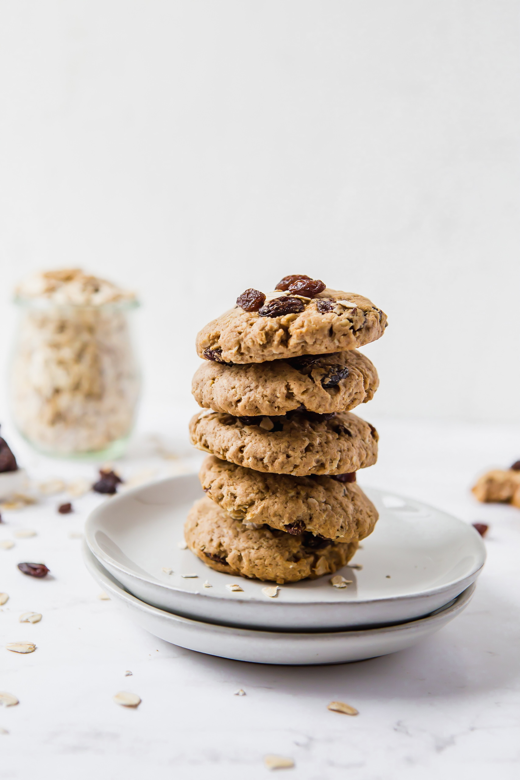 Five oatmeal raisin cookies stacked on top of each other then places on two small plates. There is a small jar of raw oats in the background on the left.