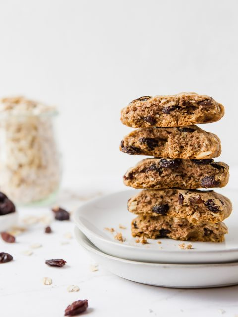 Five oatmeal raisin cookies split in half and then stacked on top of each other then places on two small plates. There is a small jar of raw oats in the background on the left.