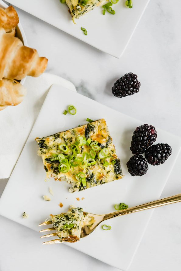 A overhead photo of a slice of egg bake with a piece on a fork laying on the plate. A few blackberries and croissants surround the plate.