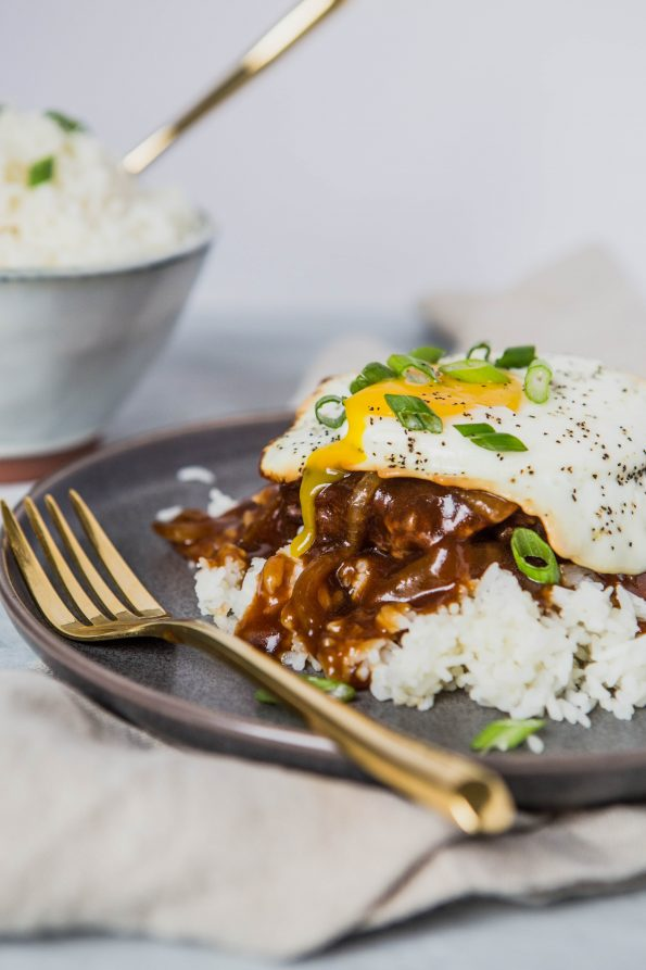 Photo of a loco loco dish on a gray plate with a bowl of rice in the background. A loco loco is white rice, hamburger patty, brown onion gravy, topped with an over-easy egg.