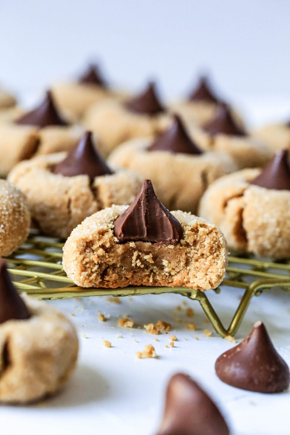 An up close shot of a peanut butter blossom cookie with a bite out of it. There are some unwrapped Hershey's Kisses in the foreground.