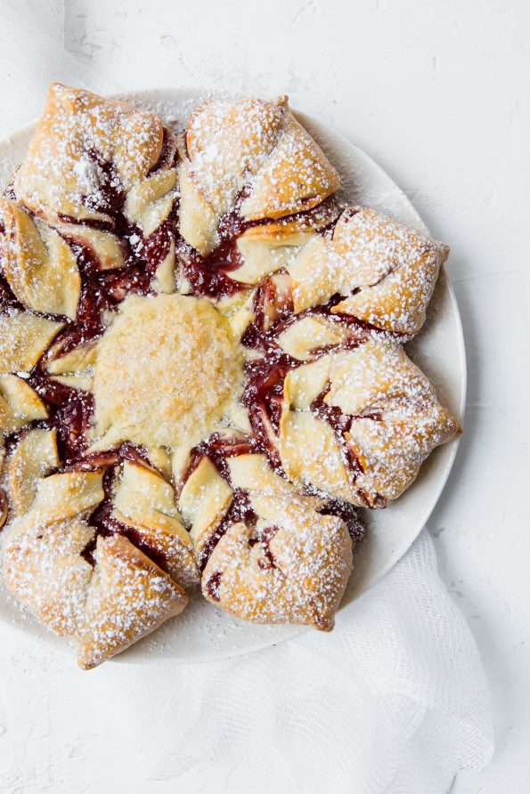 Overhead shot of a grain-free holiday star bread with raspberry filling.