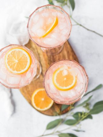 Three glasses of paloma cocktails with lemon slices and ice. They are set on a wooden cutting board with sliced lemons and grapefruits scattered around.