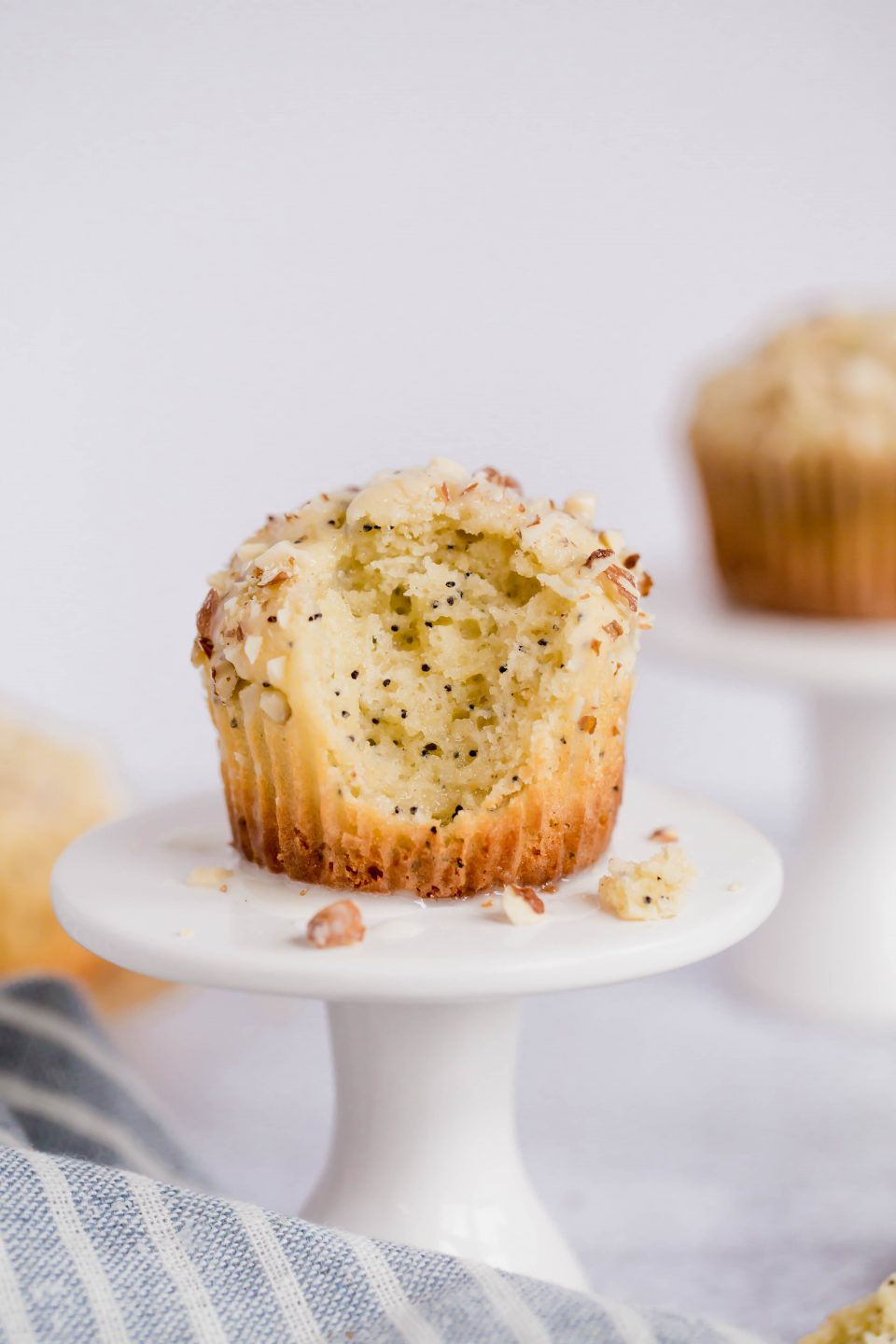 A front on shot of two gluten-free almond poppyseed muffins on small white cupcake stands. The front muffin has a large bite taken out of the top front.