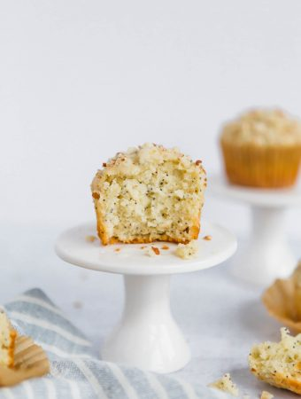 A front on shot of an almond poppyseed muffin on a small white cupcake stand. There is another cupcake in the background. In the foreground is a light-blue striped towel with pieces of muffins scattered around.