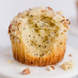 Up close shot of a gluten-free almond poppyseed muffin on a small cupcake pedestal. There is a big bite taken out of the front of the muffin.
