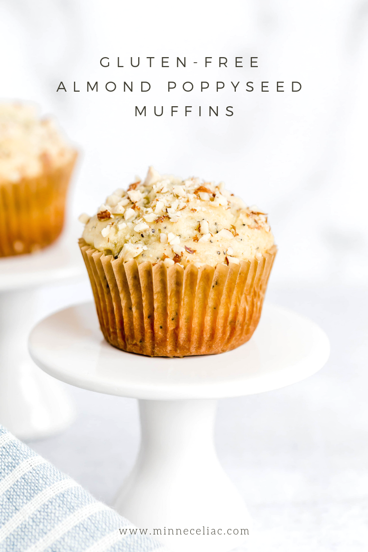 "A Pinterest graphic of a gluten-free almond poppyseed muffin on a small cupcake pedestal. The words on the graphic say ""Gluten-Free Almond Poppyseed Muffins""."