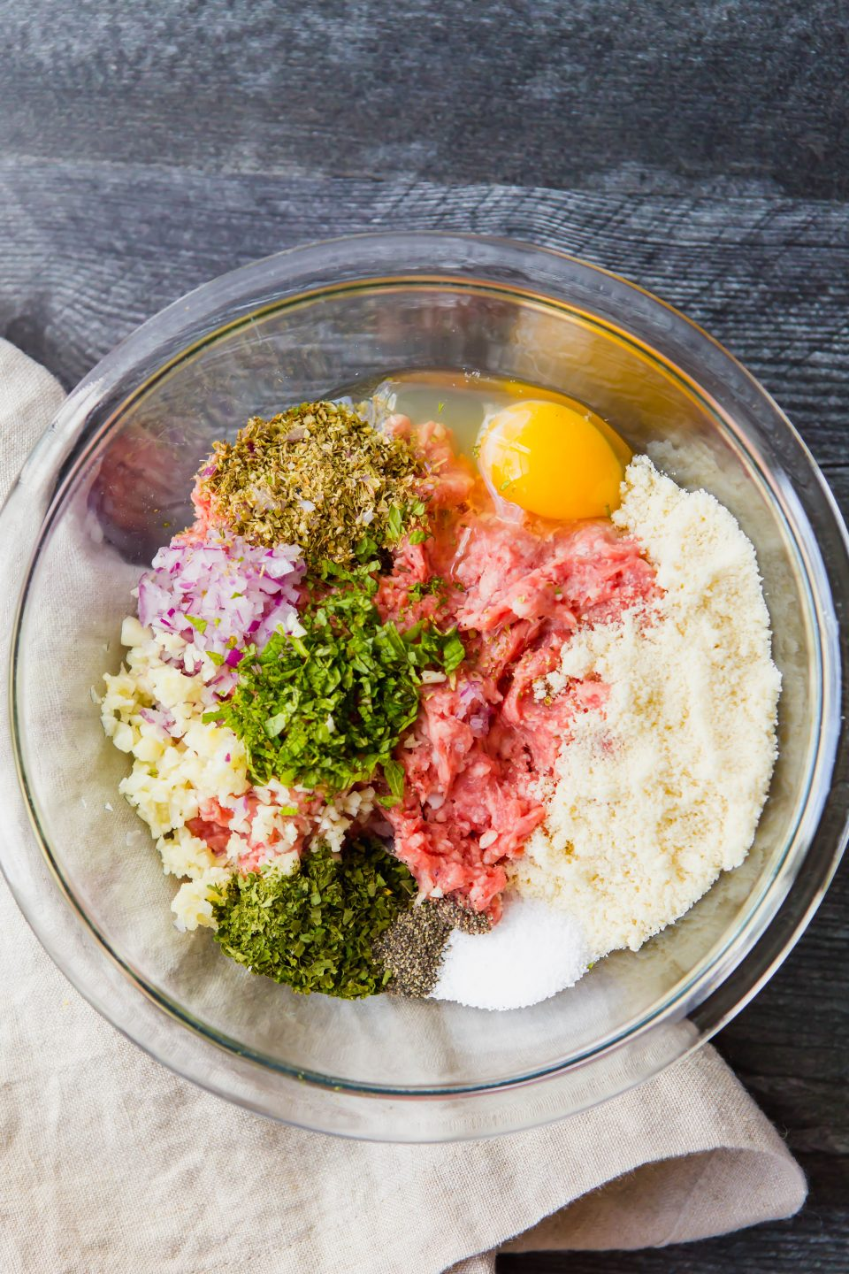 An overheard shot of a bowl with raw meatball ingredients including ground lamb, almond flour, egg, salt, pepper, red onion, oregano, garlic, and parsley.