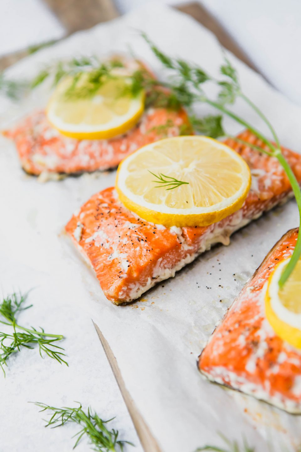 A 45 degree angle shot of three pieces of cooked salmon on parchment paper. Topped with lemon slices and garnished with dill.