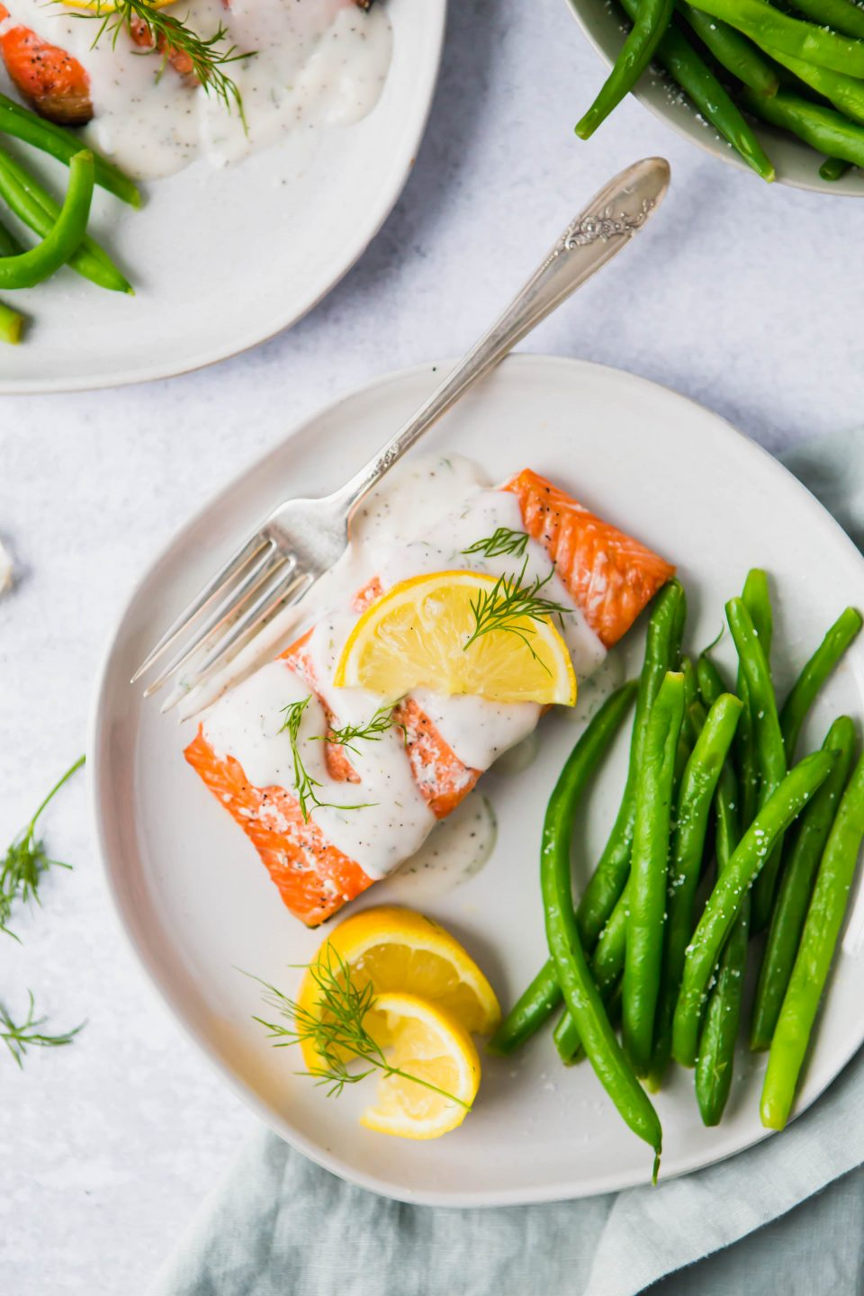 An overhead shot of a piece of salmon drizzled with a cream sauce. Lemon slices and green beans are also on the plate.